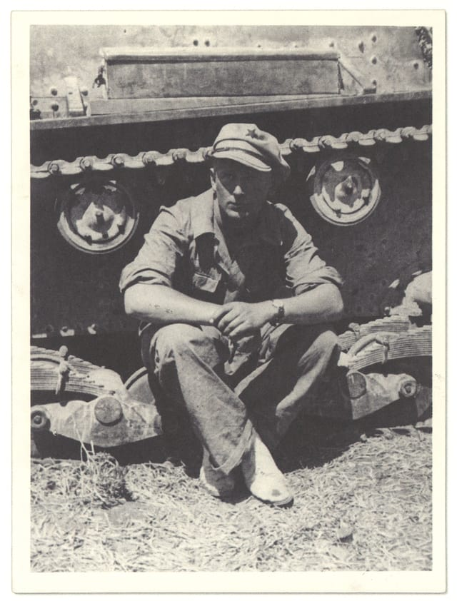Alte Fotografie von einem Mann, der vor einem Panzer sitzt.