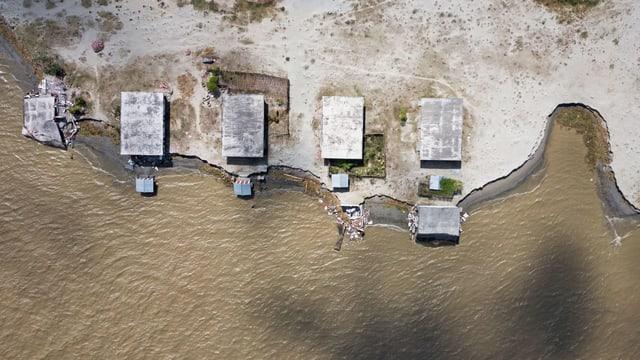 Luftaufnahme von Häusern, die an einer Küste stehen und gefährlich nahe am Wasser stehen.