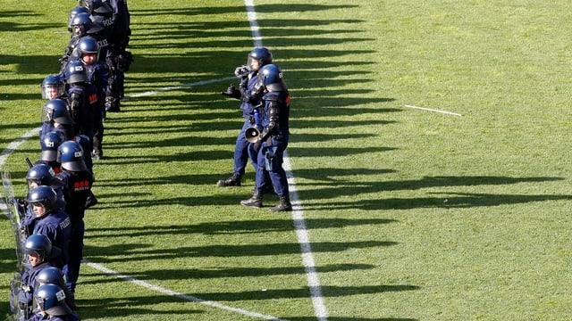 Polizisten in Kampfmontur auf einem leeren Fussballfeld