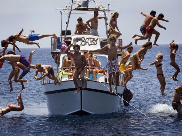 Junge Menschen springen von einem Boot ins Meer.