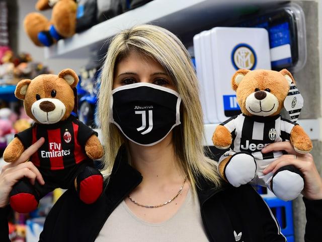 Eine Frau mit Maske hält 2 Stoffbären in den Farben von Juventus und Milan in die Höhe.