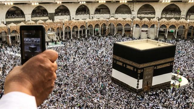 Eine Hand hält ein Smartphone, im Hintergrund ist die Kaaba in Mekka zu sehen.