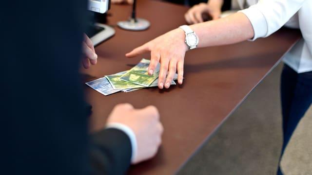 Eine Frau nimmt Noten entgegen.