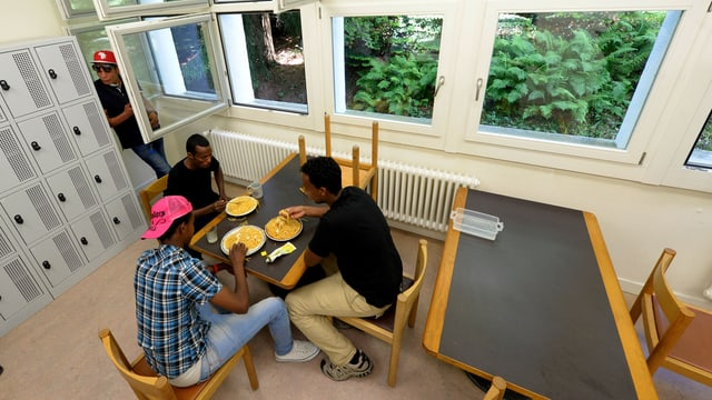 Quatter asilants en in center d'asil en Svizra.