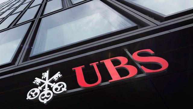 UBS-Logo, angebracht unten an einem Filialgebäude mit Glasfassade
