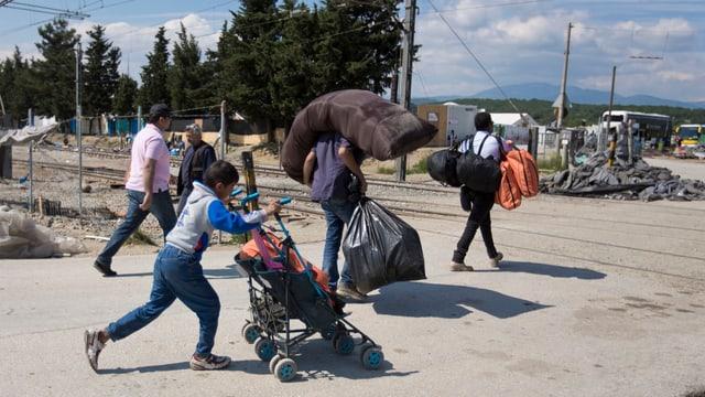 Flüchtlinge schleppen ihre Habseligkeiten