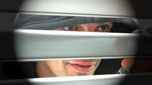 Ein Mann schaut durch die Jalousien.