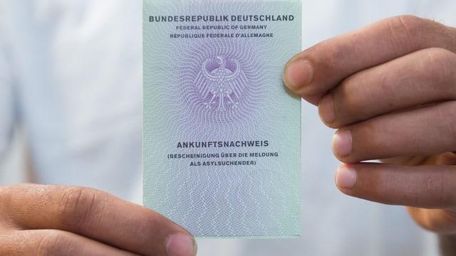 Zwei Hände halten einen Asyl-Ausweis