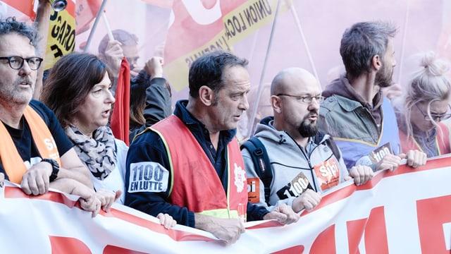 Ein Arbeiterprotest: Leute halten ein langes Plakat und demonstrieren in greller Kleidung.