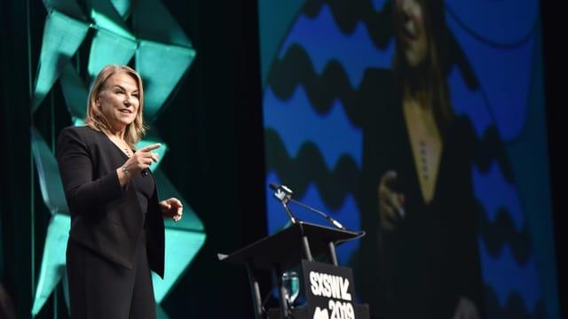 Eine blonde Frau steht auf einer Bühne und referiert. Sie trägt einen schwarzen Anzug.