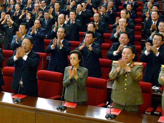 Kim Kyung Hee inmitten von zahlreichen Männern in Uniform