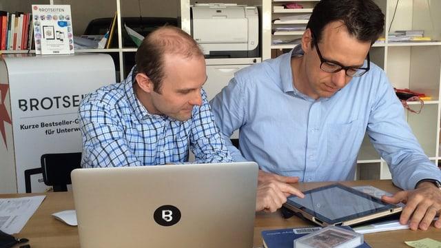 Zwei Männer schauen auf ein IPad.