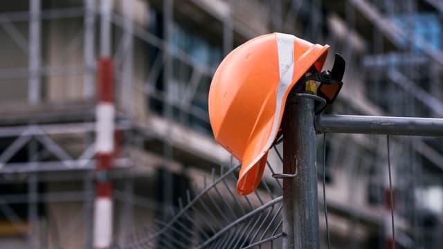 Ein Helm auf der Absperrung einer Baustelle.