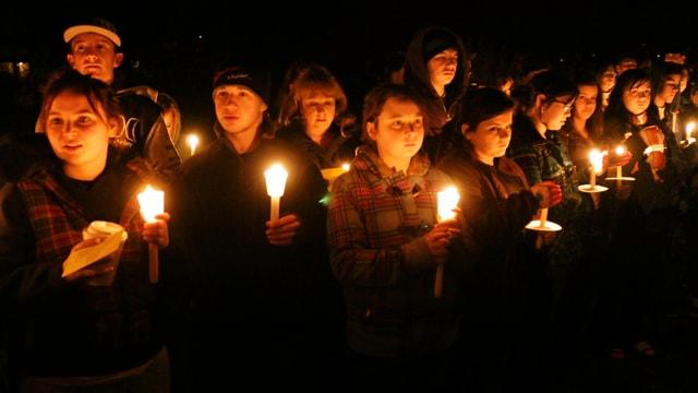Jugendliche stehen mit Kerzen in den Händen in der Dunkelheit.