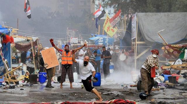 Menschen schleudern Gegenstände, im Hintergrund zerfallene Protestcamps.