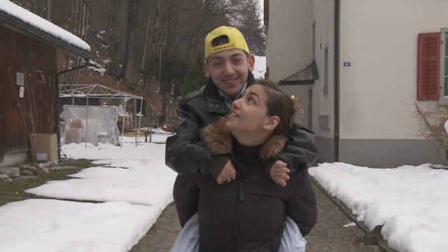 Ayse Yilmaz trägt ihren Sohn auf dem Rücken.