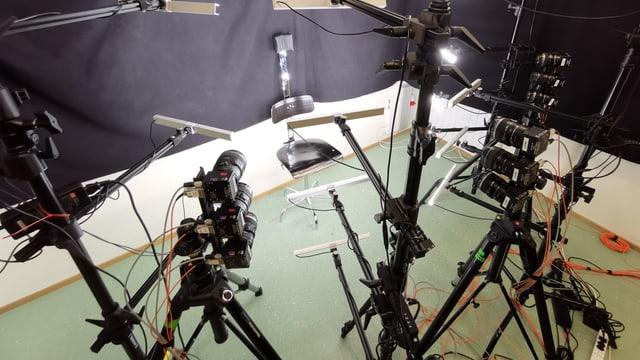 Viele Stative, Kameras darauf, Beleuchtung und im Zentrum ein einfacher Dreh-Stuhl, der unbequem wirkt.