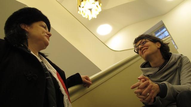 Beide stehen beziehungsweise sitzen auf der Treppe des Foyers im Stadttheater Solothurn und diskutieren.