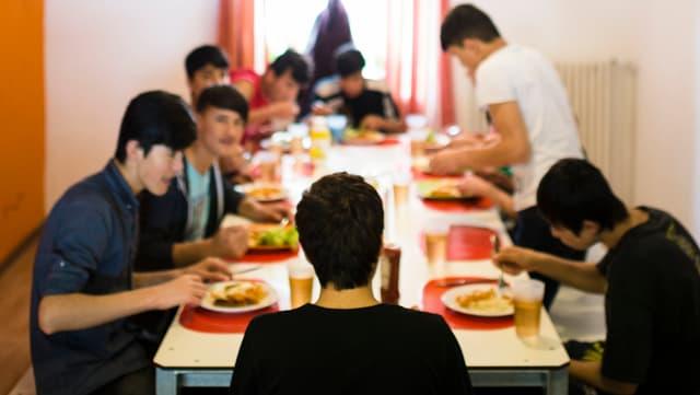 Minderjährige unbegleitete Asylsuchende sitzen beim Mittagessen