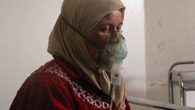 Syrierin mit Kopftuch und Sauerstoffmaske.