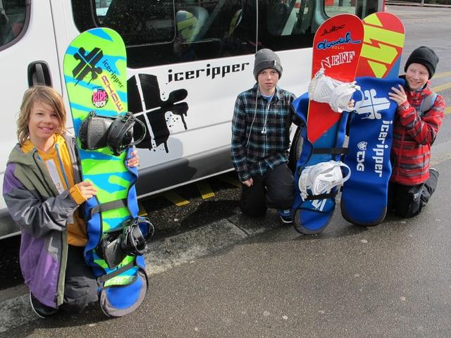 3 Kinder posieren mit Snowboard vor einem Bus