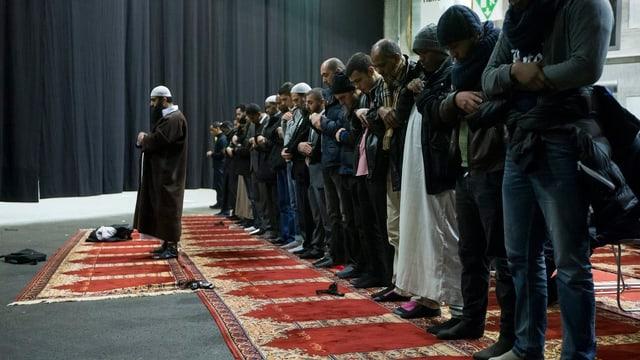 Betende Muslime auf Teppich stehend