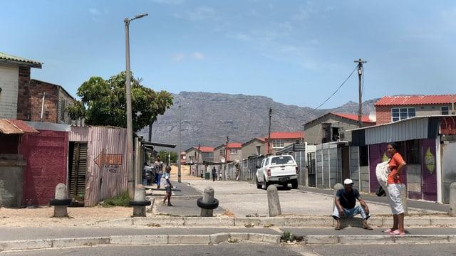 Mann und Frau auf Strasse, im Hintergrund sieht man den Tafelberg