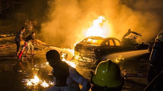 Menschen versuchen, brennende Autos zu löschen