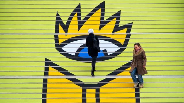 Zwei Frauen bewegen sich vor dem Logo der Leipziger Buchmesse, das ein grosses Auge zeigt.