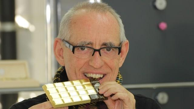 Walter Wolf Windisch mit einer Tafel Schokolade aus Kuhmist und Blattgold.
