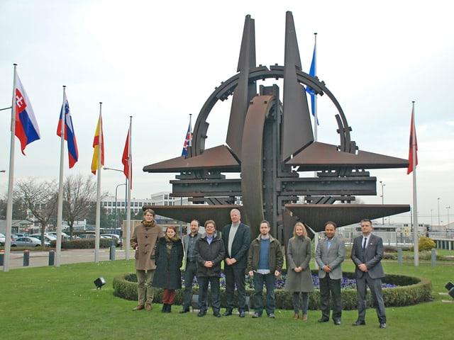 UNO-Korrespondenten in Brüssel beim Nato-Hauptsitz vor einem Kunstwerk.