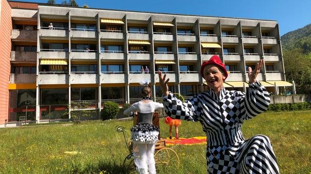 Ein Clown kniet in einer Wiese, im Hintergrund ist ein Altersheim, die Leute stehen auf den Balkonen.