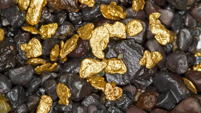 Nahaufnahme von glänzendem Goldflitter zwischen Kieselsteinchen