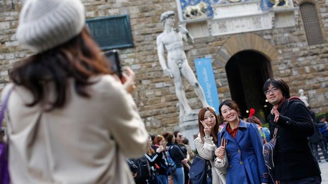 Asiatische Touristen posieren vor der David-Statue in Florenz.
