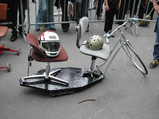 Zwei Bürostühle, fest gemacht auf einer Holzplatte mit rädern, davor die vodere Hälfte eines Velos mit Lenker und einem Rad.