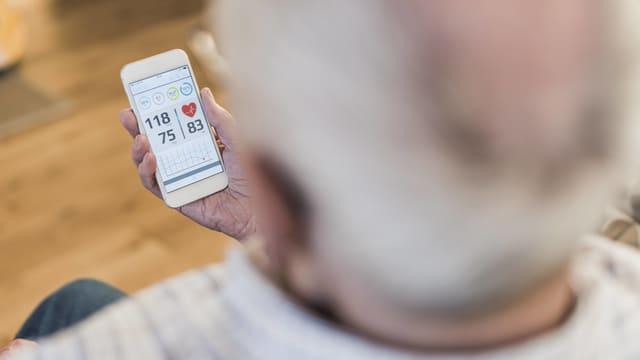 Ein älterer Mann liest auf dem Smartphone seine Blutdruckdaten ab.