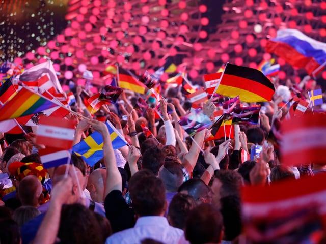 Viele Hände die verschiedene Nationalflaggen hochheben.