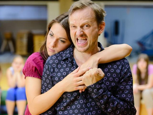 Eine Frau hält einen Mann (Milan Peschel) im Arm.