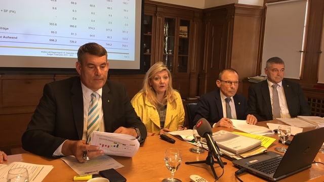 Drei Regierungsräte und eine Regierungsrätin präsentieren Zahlen.