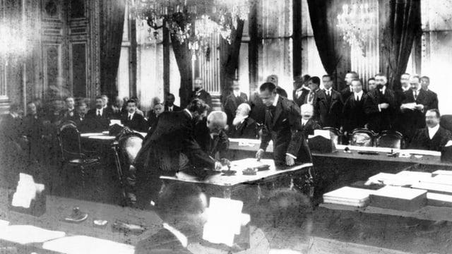 Schwarzweiss-Bild: Männer in Fräcken beim Unterzeichnen eines Vetrags.