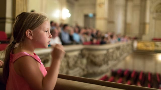 Ein Kind auf dem Balkon eines Konzertsaals.