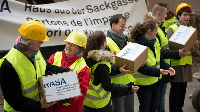 Initianten mit gelben Bauhelmen und Kartons mit Unterschriftenbögen.