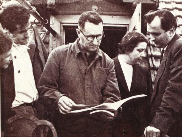 Brecht hält ein Manuskript in den Händen. Um ihn stehen vier Freunde.
