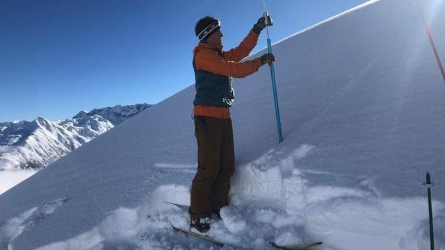 Der Bergführer sticht in den Schnee.