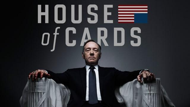 """Ein Mann sitzt auf einem Thron aus Stein. Über ihm steht die Inschrift """"House of Cards"""", auf Deutsch """"Das Kartenhaus""""."""