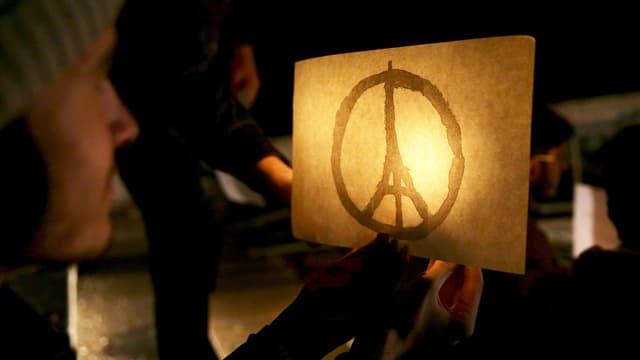 Ein Mann hält ein Bild mit einem Eiffelturm im Friedenszeichen. Es ist beleuchtet.