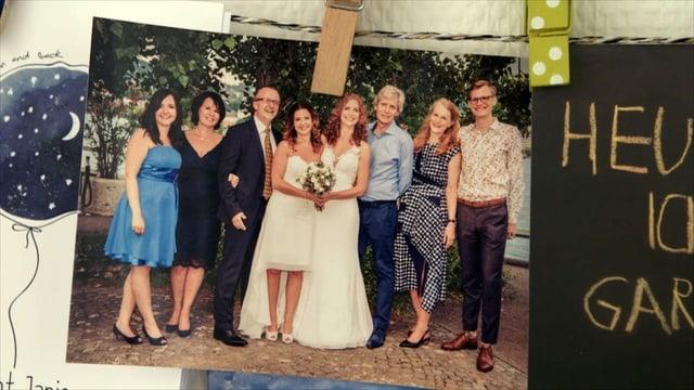ein Hochzeitsfoto mit zwei Bräuten und deren Familien