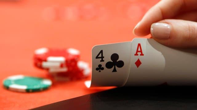 Eine Frauenhand zeigt Spielkarten mit einem 4 Pique und einem Caro Ass. Im Hintergrund liegen Jettons vom Pokerspiel.