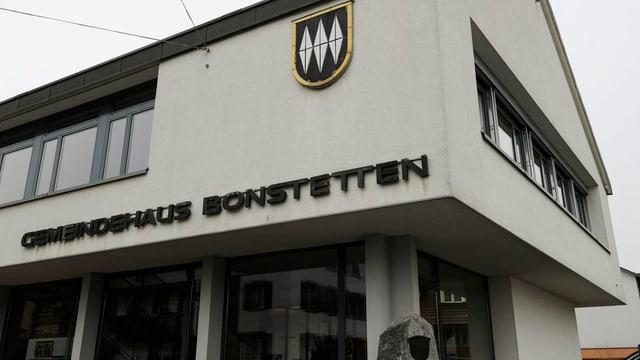 Das Gemeindehaus von Bonstetten, unten sind grosse Glasfenster, oben an der Hauswand sieht man das Gemeindewappen.