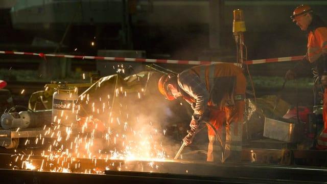 Ein Gleisarbeiter beim Schweissen der Schienen. Es ist Nacht und man sieht den Funkenflug.